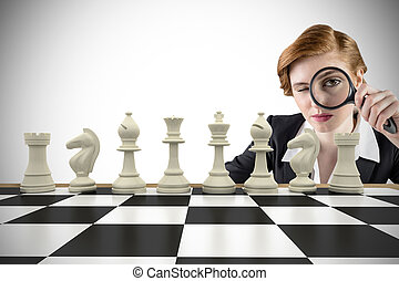 Composite image of focused businesswoman with magnifying glass