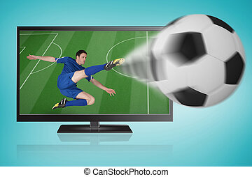 Composite image of football player in blue kicking ball out of tv against blue vignette