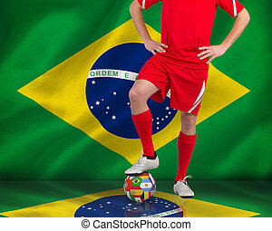 Composite image of football player standing with ball