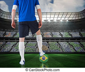 Composite image of football player standing with brasil ball