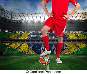 Composite image of football player standing with flag ball