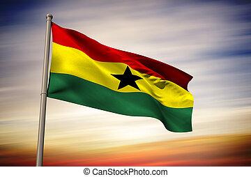 Ghana national flag against blue cloudy sky