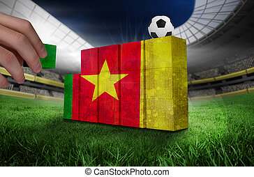 Hand building wall of cameroon flag in grunge effect