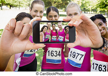 Hand holding smartphone showing confident female participants of breast cancer marathon