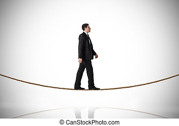 Composite image of handsome businessman stepping on tightrope