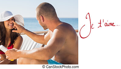 Composite image of handsome man applying sun cream on his girlfr