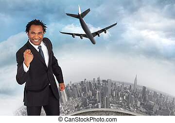 Composite image of happy businessman with fist