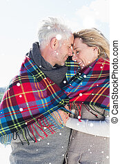 Composite image of happy couple wrapped up in blanket standing o