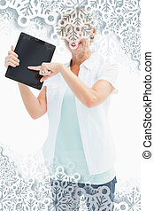 Composite image of happy mature woman pointing to tablet pc