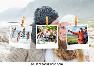 Composite image of instant photos hanging on a line against couple on the beach