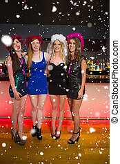 Composite image of laughing friends having a hen party at the ba