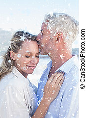 Composite image of man kissing his smiling partner on the forehe