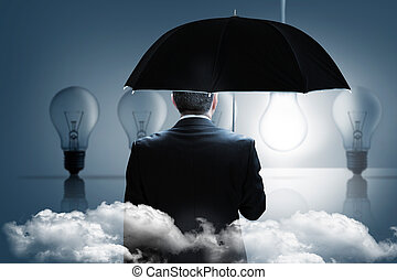 Composite image of mature businessman holding an umbrella