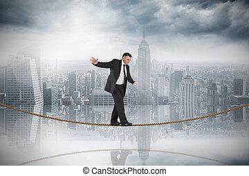 Composite image of mature businessman doing a balancing act...
