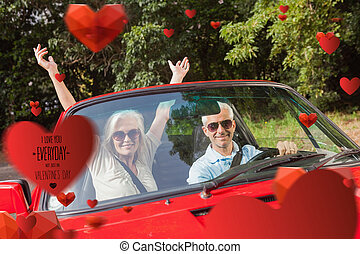 Composite image of mature couple in red cabriolet cheering...