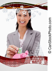 Composite image of money being put into piggy bank by smiling bu