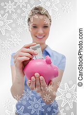 Composite image of money being put into piggy bank by woman
