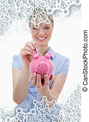 Composite image of note being put into piggy bank by woman