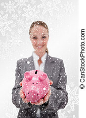 Composite image of piggy bank being held by smiling bank employe