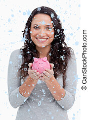 Composite image of piggy bank being held by smiling woman
