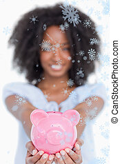 Composite image of pink piggy bank held by a young smiling woman