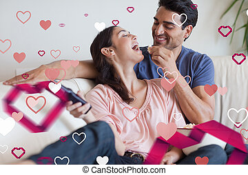 Composite image of playful couple watching tv while eating popco