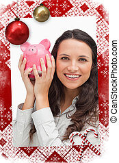 Composite image of portrait of a brunette shaking a piggy bank