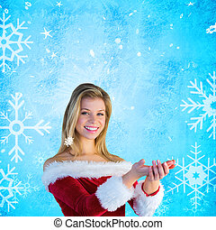 Composite image of pretty girl holding hands out in santa outfit