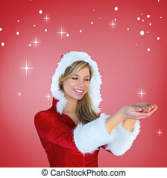 Composite image of pretty santa girl holding hands out