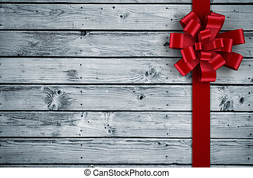 Red christmas bow and ribbon against digitally generated grey wooden planks