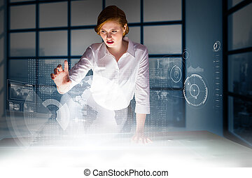 Redhead businesswoman using interactive desk against room with large window showing city