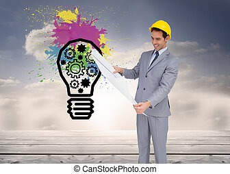 Composite image of smiling architect with hard hat looking at plans on white background