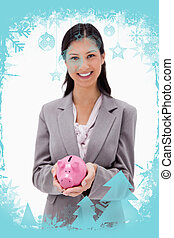 Composite image of smiling businesswoman with piggy bank