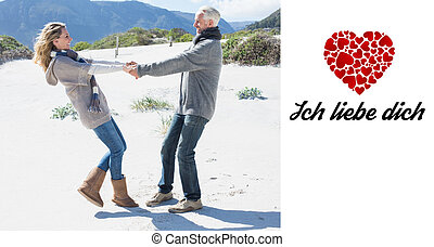 Composite image of smiling couple spinning on the beach in warm