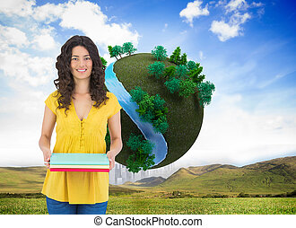 Composite image of smiling curly haired brunette holding notebooks