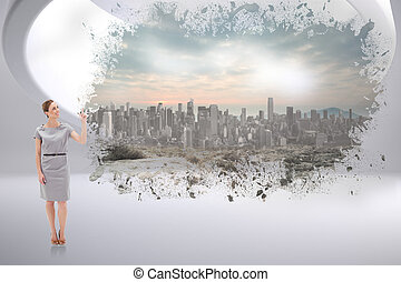 Composite image of smiling woman in a dress pointing upwards