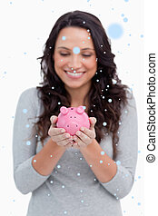 Composite image of smiling woman looking at piggy bank in her ha