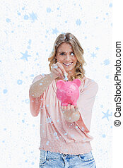 Composite image of smiling woman putting money into a piggy bank