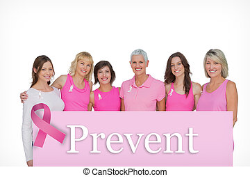 Composite image of smiling women wearing pink for breast cancer