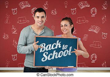 Composite image of smiling young couple pointing at sign they ar