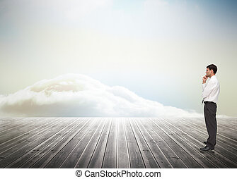 Thoughtful young businessman looking away against clouds on the horizon