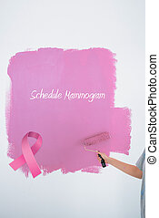 Composite image of woman painting her wall pink