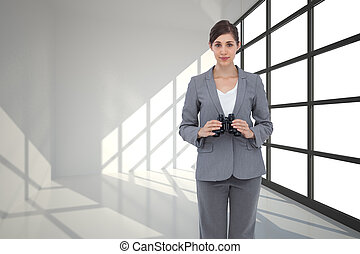 Composite image of young businesswoman with binoculars