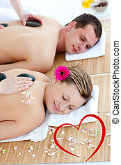 Composite image of young couple enjoying a back massage with sto