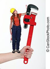 Composite of a woman with an adjustable wrench