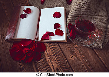 Composition consist of roses, hibiscus tea cup and note book on a wooden surface
