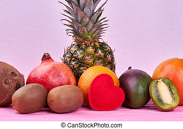 Composition from exotic fruits on pink background.