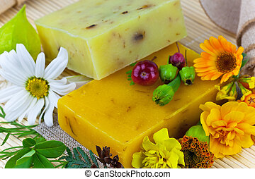 Macro view of natural soap and flowers on the mat