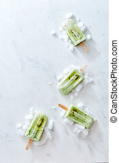 Composition in the form of a corner frame of ice cream on a stick with a piece of kiwi and ice on a gray marble background. Space for text. Flat lay