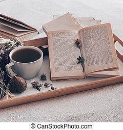 Composition of a cup of tea and opened book is not readable on a coffee table in the room, with figs and flowers. close up
